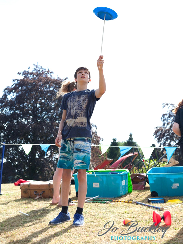 Child plate spinning at a Thomas Trilby circus skills school workshop outdoors